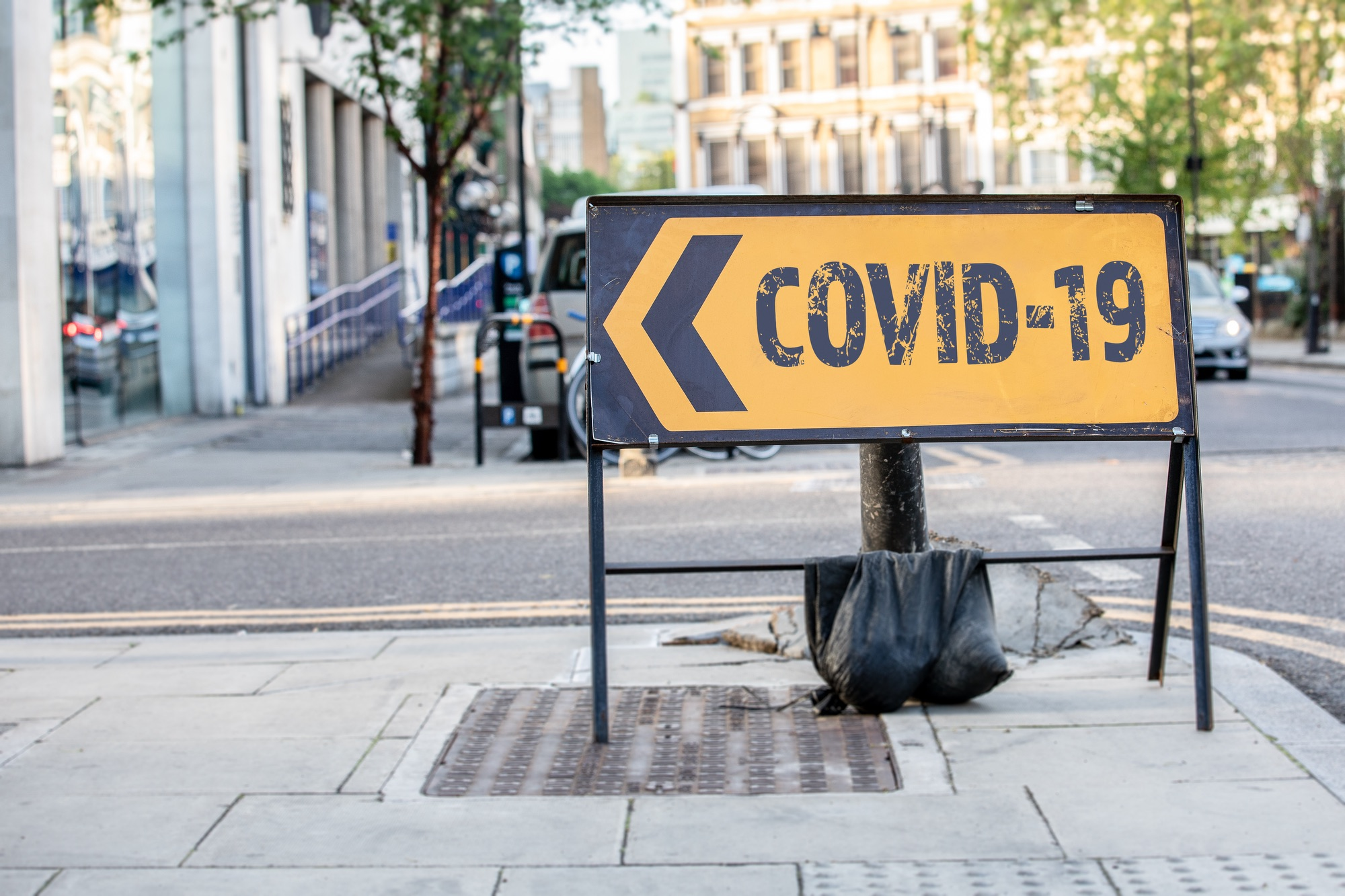 SS_COVID-19 Coronavirus - outbreak of desease that was first reported from Wuhan, China. Yellow diversion road sign in a UK city street