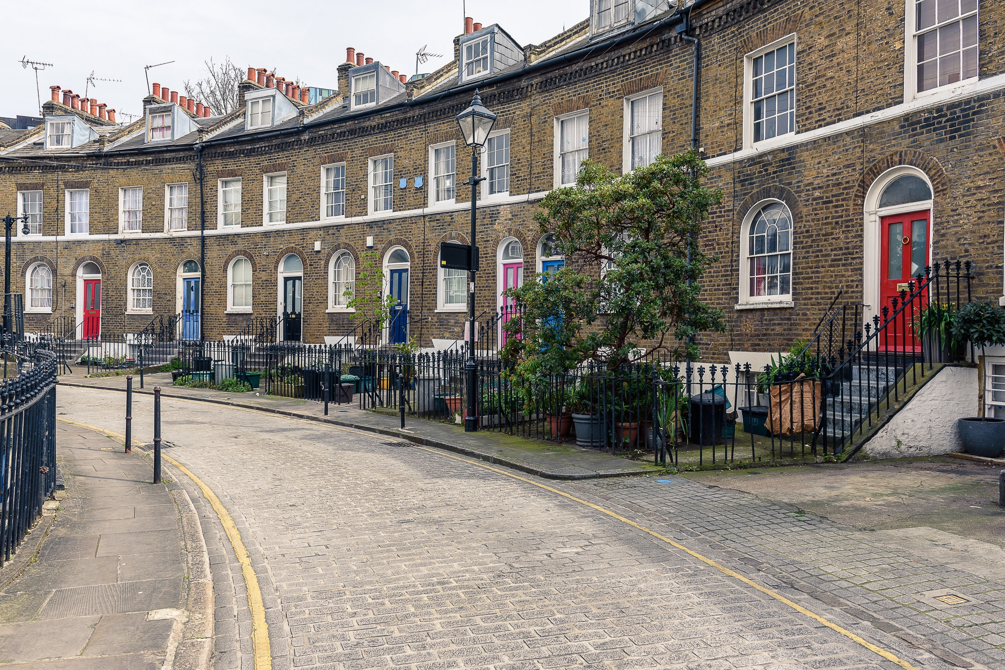 SS_A typical british road with houses in London, with colored doors and fireplaces on the roofs
